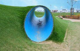 Kunstrasen Spielplatz mit Kriechröhre