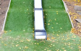 Kunstrasen Hügel mit Fallschutz – Edelstahlrutsche als Wellenrutsche
